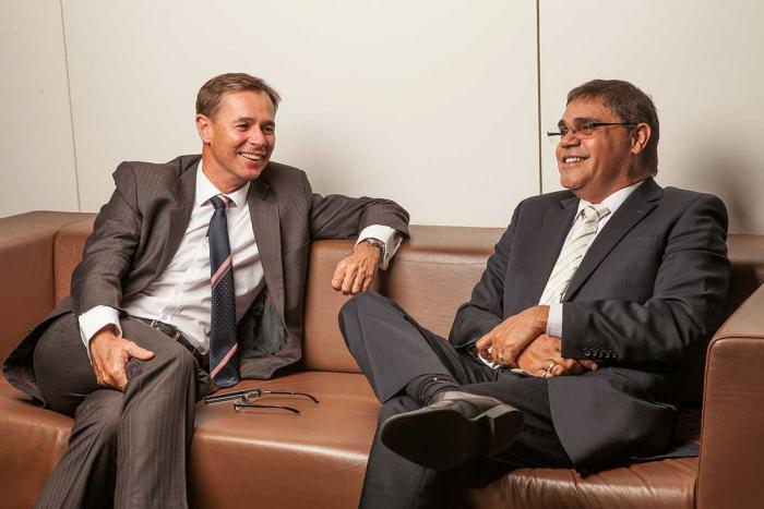Man on left in brown suit and another man on right in dark grey suit sit on a brown couch with legs crossed and smiling.
