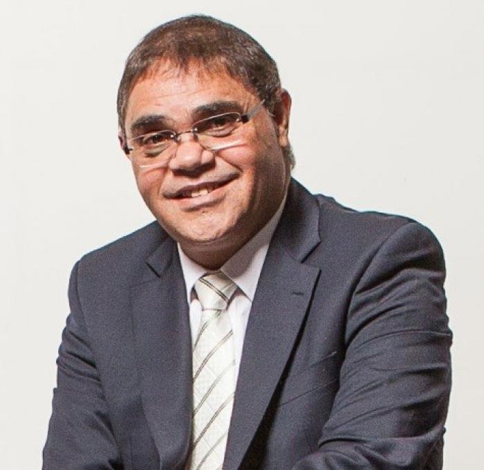 Aboriginal man in suit and wearing glasses.