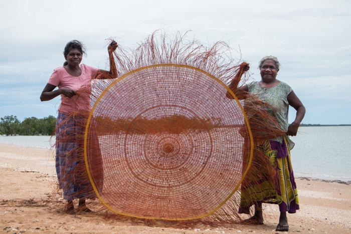 Two Aboriginal women stand on a beach with water and trees in the background. They support a finely weaved circular item between them which stands almost as high as them.