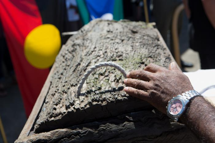 The hand of an Aboriginal man, wearing a silver watch, gently lays on top of a traditional wood box. The Aboriginal and Torres Strait Island flags can be seen in the background.