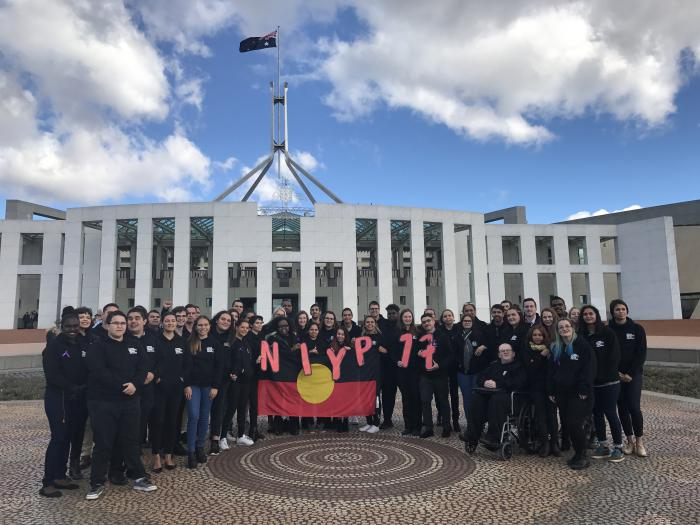 Group of Indigenous young adults dressed mainly in black tops stand in front of the Australian Parliament House holding the Aboriginal flag and the letters and numbers N.I.Y.P. 17