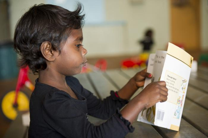 Pictured is an Indigenous school aged boy in a classroom reading a school book.