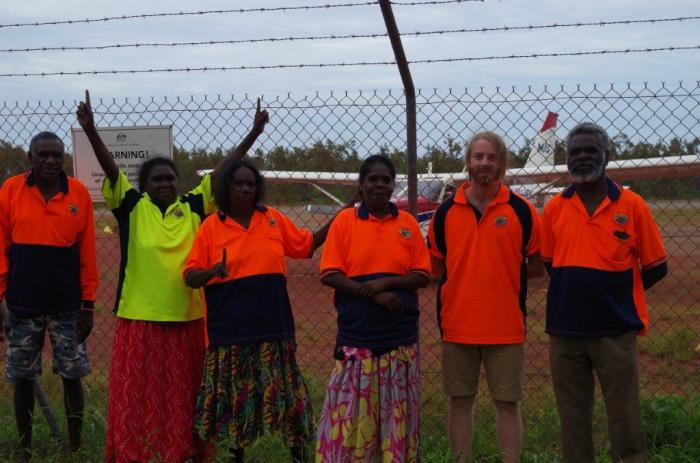Five Aboriginal people and one non-Aboriginal person are standing in front of a remote airfield. In the background is a small airplane.