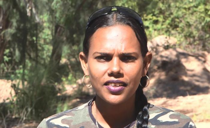 Aboriginal woman in cargo shirt and hair in plat looks at camera with trees in the background.