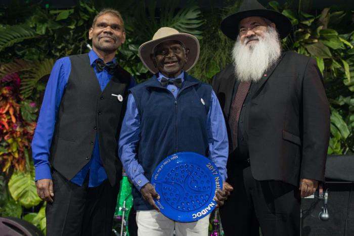 An elderly Aboriginal man holds a large blue plate with a younger Aboriginal man standing to his right and an Aboriginal man with a grey beard standing to his left.