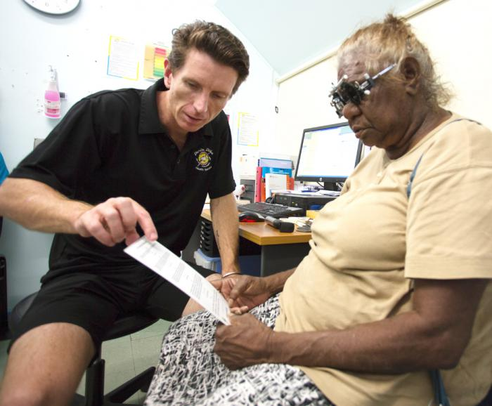 Optometrist Luke Arkapaw performing an eye check on an Indigenous woman