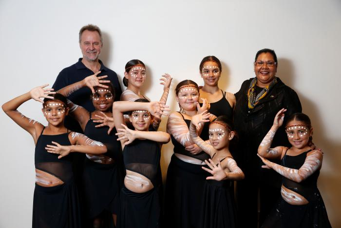 Non-Indigenous man and Aboriginal woman stand in front of white background with young female Indigenous dancers between and in front of them. All are dressed in black and the dancers wear white face paint.