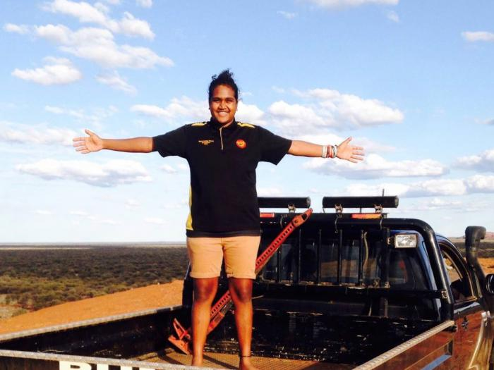 A smiling young adult Aboriginal woman dressed in light shorts and dark top stands in the back of a ute with her arms spread wide. In the background is a flat, arid landscape.