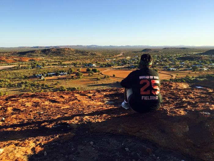 Aboriginal woman sits on a hill overlooking a small town surrounded by low hills in an arid landscape. On the back of her dark top is 'Squad of 2017, 25, Fielding'.