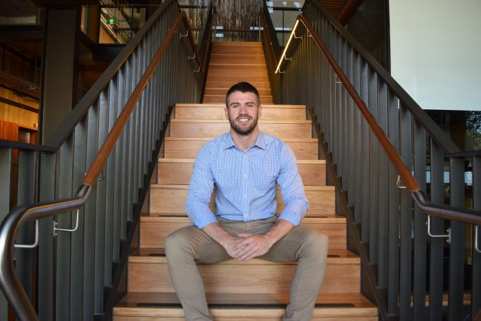 Young adult man wearing blue shirt and light brown pants sits on wooden staircase with grey railings to balustrade.