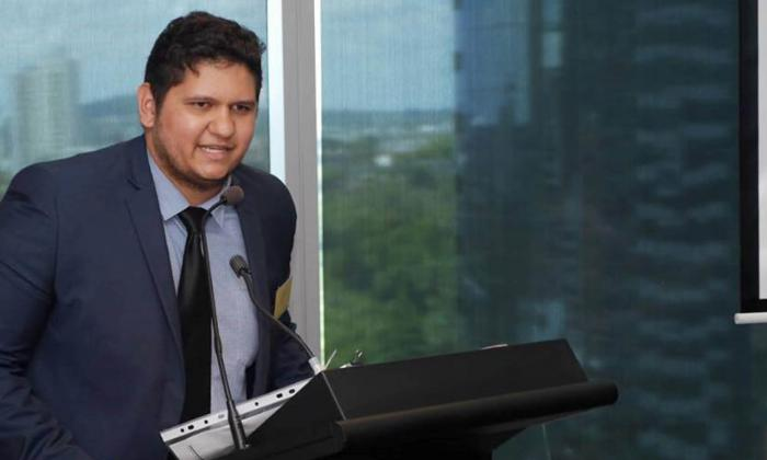 A young Aboriginal man wearing a suit and tie is speaking at a rostrum.