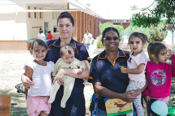 Two Indigenous women in dark blue shirts hold or support four Indigenous children, the group stand in front of a brick building mostly painted white with trees nearby.