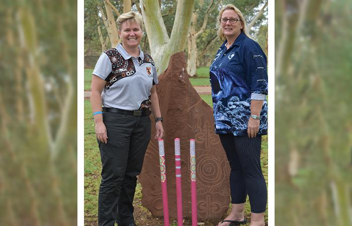 Two women stand either side of a rock slab sculpture with Indigenous designs in front of which are three cricket stumps coloured pink and decorated with colourful Indigenous designs. The woman on the left wears dark trousers and a grey and brown shirt.