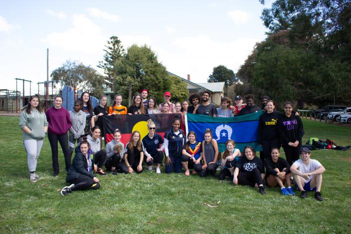 Group of Indigenous youth sit or stand on grass, some holding the Aboriginal flag and Torres Strait Islander flag. In the background is a building, cars and trees.