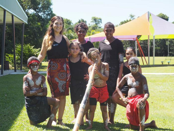 An adult woman and seven Indigenous youth stand or kneel on a lawn. To the left is a building and in the background a canopy. Some of the youth wear paint in traditional patterns and wear traditional clothing while one holds a didgeridoo.