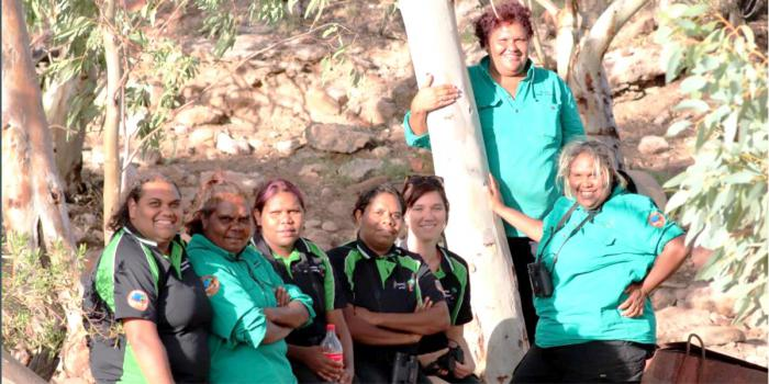 Seven Aboriginal women in ranger uniforms stand next to a white bark tree. In the background is a rocky slope and more trees.