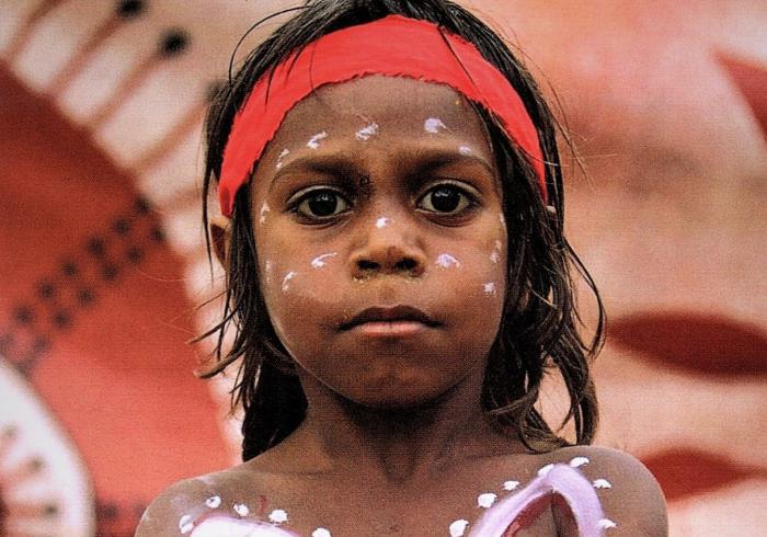 Aboriginal boy in body and face paint standing in front of Aboriginal artwork