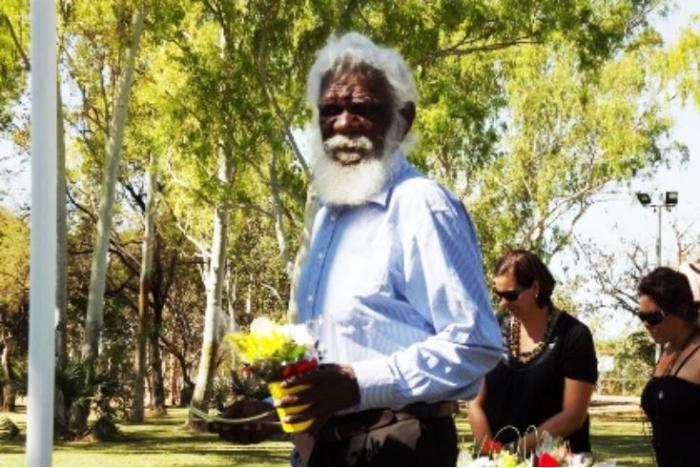 Elderly Aboriginal man with white hair and beard and dressed in pale blue shirt is holding a pot of flowers. In the background are two women dressed in black and a line of tall leafy trees.