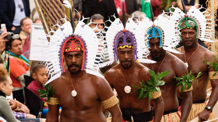 For bare chested Indigenous men in traditional headress (dari) walk past a crowd of mainly Indigenous onlookers.