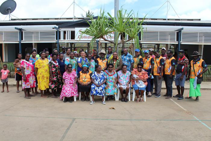 A large group of Indigenous people stand or sit in front of a building and a tree. All are dressed in colourful clothing.