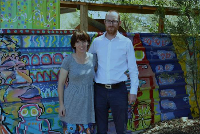 A woman in a grey dress and colourful tights and a man in white shirt and blue trousers stand in front of a painted fence featuring a face, a bicycle and other designs of blue, green, red, yellow and purple.