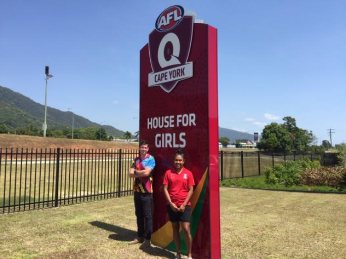 Adult male in multi-coloured shirt and adult female in red shirt stand in front of a large red sign which says AFL Cape York House for Girls. In the background is grass, a road, some buildings and hills.