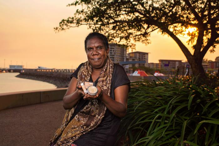 An Aboriginal woman in dark dress and patterned scarf sits next to a bush and holds three small containers in her hands. In the background is water, a wharf, a tree and buildings.