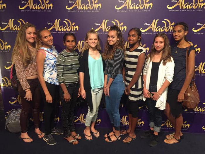 Eight young Indigenous women standing on a carpeted floor in front of a poster wall with multiple displays of the word 'Aladdin'.