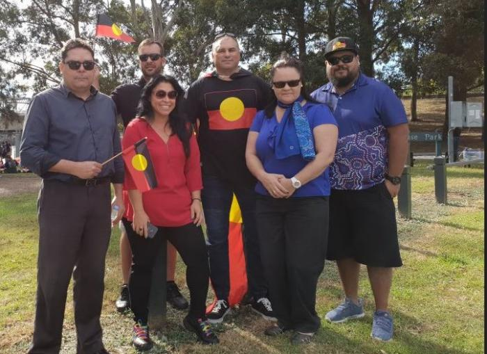 Six Aboriginal adults in casual clothing stand on grass. Some hold the Aboriginal flag. In the background are trees.