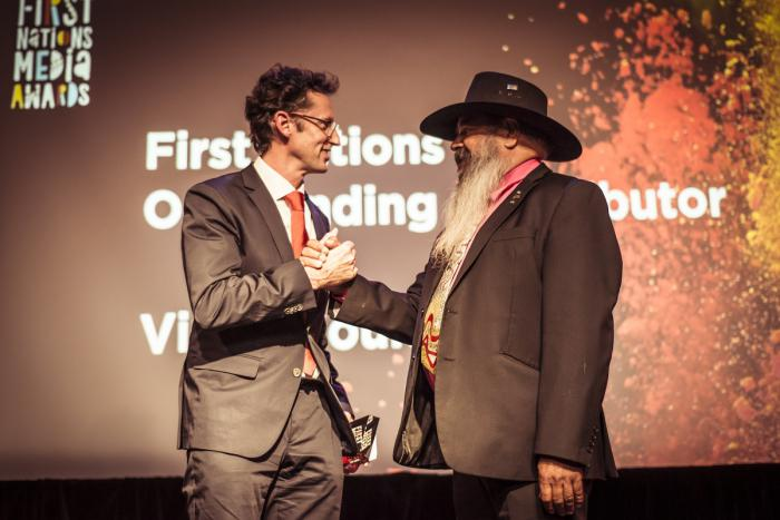 Two men in suits, one in hat and beard stand before a backdrop with the words: First Nations Media Awards First Nations Outstanding Contributor Award