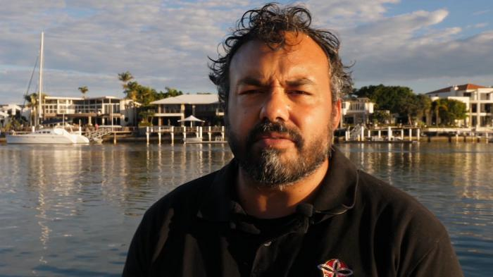 Indigenous man in black polo shirt faces camera. In the background is water and behind that, a boat, wharfs, buildings, trees and a cloudy sky.