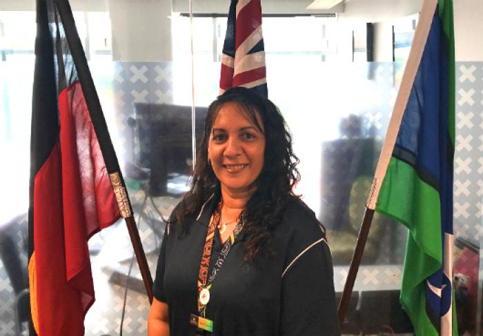Indigenous woman with long black hair wearing black clothing stands in front of the Aboriginal, Australian and Torres Strait Islander flags. In the background is a glass wall behind which is an office.