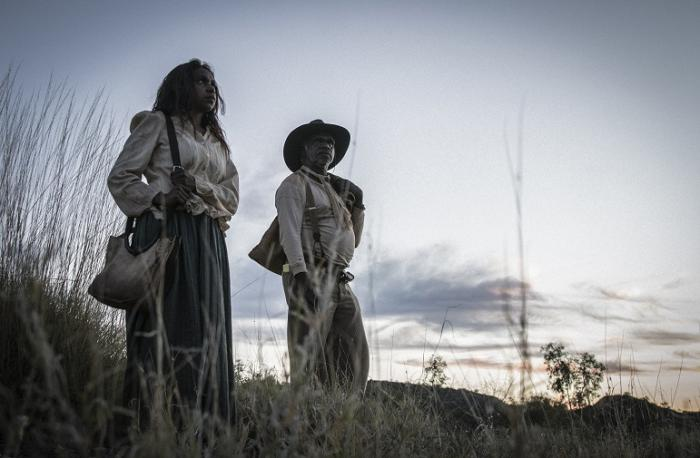 Indigenous woman in white shirt and dark skirt with handbag over shoulder stands next to Indigenous man with hat, light shirt and pants standing in the outback with sunset behind.