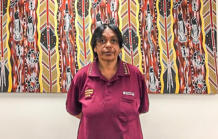 Aboriginal woman in maroon polo shirt stands in front of an Aboriginal painting of featuring vertical patterns of lines and animals and spears and other figures.