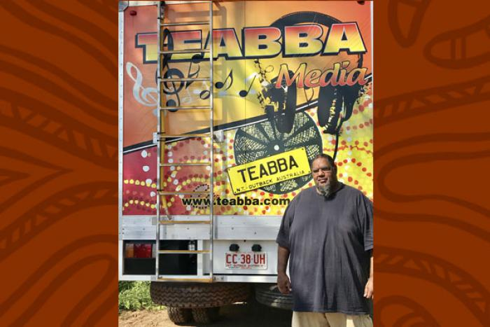 Aboriginal man in grey shirt stands in front of the rear door of a truck. The door is painted with red, yellow and black designs and includes the following words: TEABBA Media, TEABBA N.T. Outback Australia, www.teabba.com
