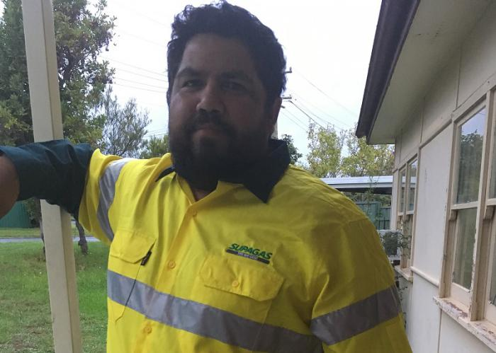 An Aboriginal man with beard and wearing a yellow safety shirt stands next to a beige coloured building. In the background is green grass, trees and another building.