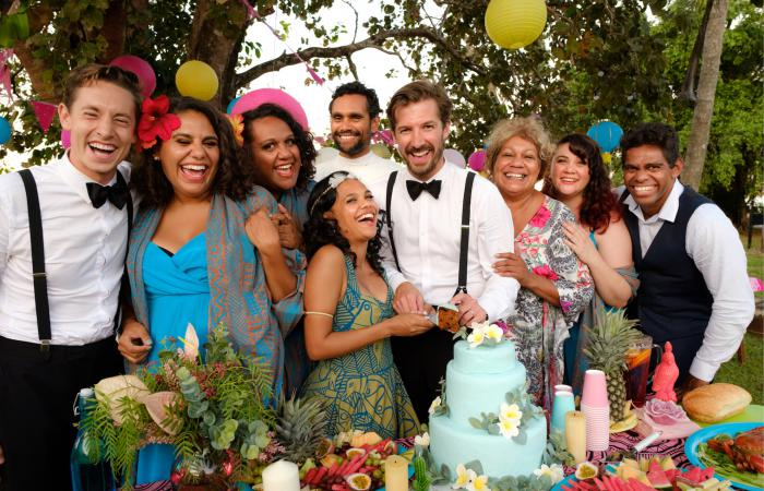 There are 9 men and women facing the camera. They all smiling and some are laughing. They are dressed for a wedding. A bride and groom are cutting a wedding cake.