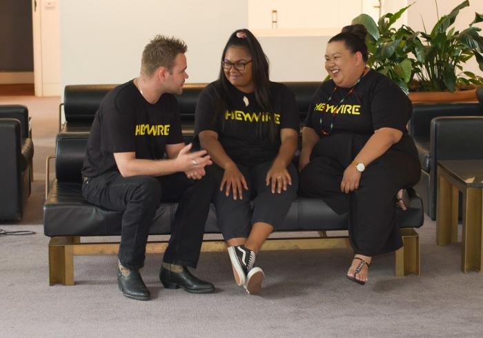 One Indigenous man and two Indigenous women dressed mainly in black, sit on a black couch. In the background is a white wall and some indoor plants. On the floor is a grey carpet.