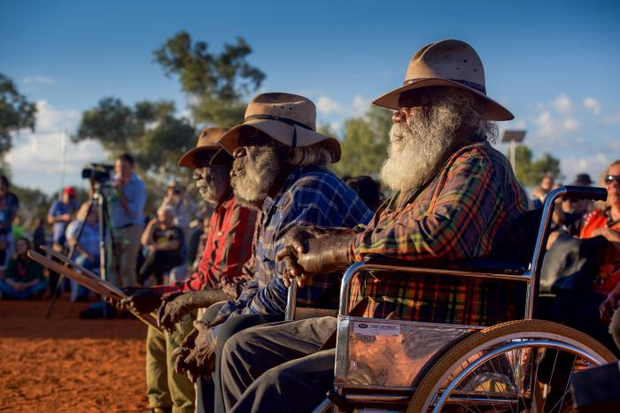 Three elderly Indigenous men in hats sit in foreground, the first in a wheelchair, with crowd and trees in background. The sky is blue and the soil is ochre.
