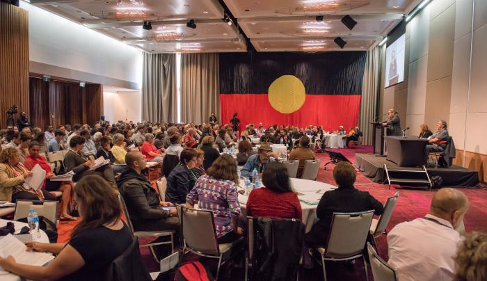 Large gathering of people in a hall, one standing at a rostrum and most seated at tables or on seat rows. The carpet is red, the walls are beige and the curtains are brown. Covering the far end wall is the Aboriginal flag.