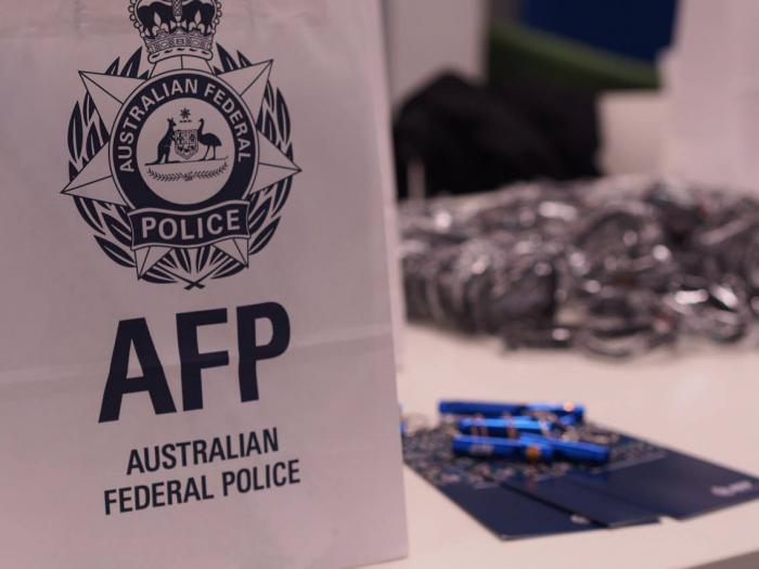 White paper bag with a logo of a crown sitting on a seven pointed star and the letters AFP and words Australian Federal Police, sits on a table next to pens and pamphlets with other material in the background.