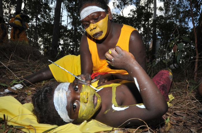 Child on ground being painted by woman to get ready for the Garma Festival.