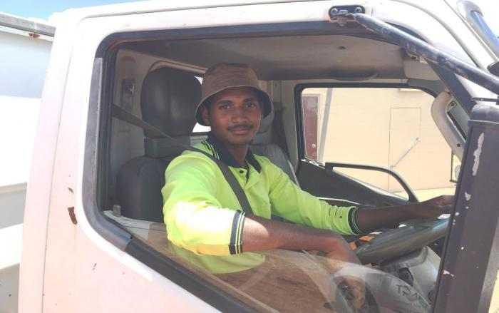 An Indigenous young man wearing work wear sits in the cab of a truck.
