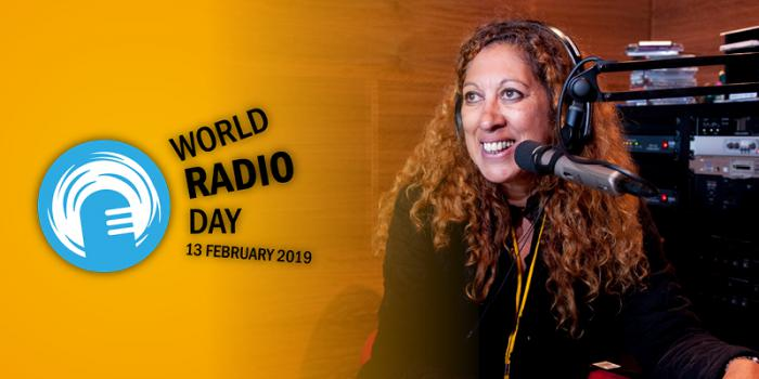 Indigenous woman with long hair in front of a microphone is smiling. Behind her is radio apparatus and to left is a blue and white logo and teh words World Radio Day 13 February 2019