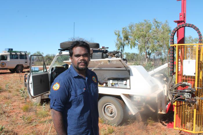 A young Aboriginal man, Wynston Shovellor-Sesar, stands in front of vehicle and other machinery.
