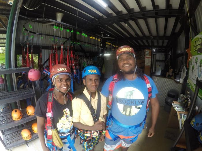 Three youth stand in a small room. Each wears a helmet and straps set up for abseiling. In the background are racks of helmets and other climbing gear.