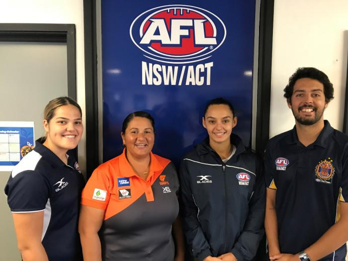 Three women and one man wearing AFL polo shirts stand in front of a large sign which says AFL NSW/ACT.