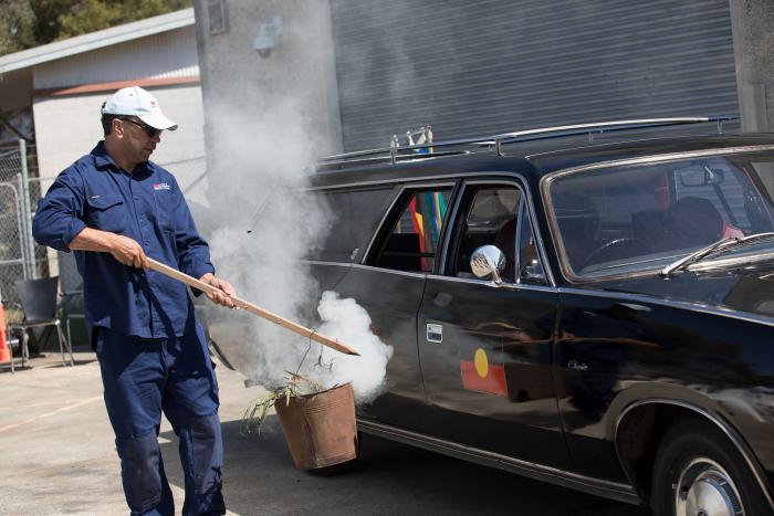 An Aboriginal man wearing blue shirt and pants, holds a wooden stick with a metal bucket on the end. Smoke and gum leaves are in the bucket. A black hearse with an Aboriginal flag on the door is in the background.
