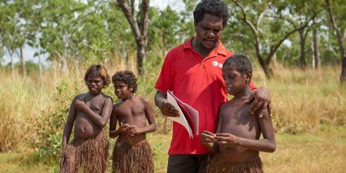 Two Aboriginal boys in grass skirts stand at left and behind an Aboriginal man in a red shirt and boy in a grass skirt in the foreground. The man holds some papers on which he and the third boy are focussed. In the background is long grass and trees.
