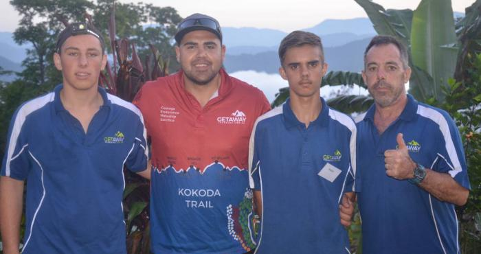 Two adult males and two young men dressed in mainly blue shirts, stand arm in arm in front of tropical foliage atop a mountain. In the background is mountain terrain and low-lying cloud.